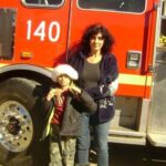 Laurie Millard and Daniel in front of the firetruck.